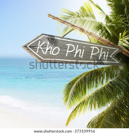 Wooden sign Kho Phi Phi on tropical white sand beach summer background. Lush tropical foliage and sunshine. Blue ocean at perfect day. No people. - stock photo