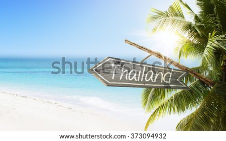 Wooden sign Paradise on tropical white sand beach summer background. Lush tropical foliage and sunshine. Blue ocean at perfect day. No people. - stock photo
