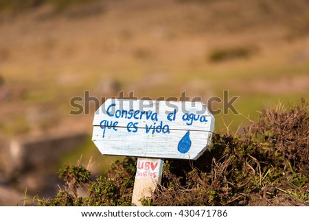 Wooden sign post saying in Spanish: Save the water in the countryside with bokeh background. Merdia - stock photo