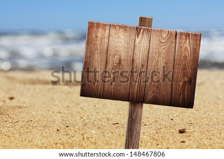wooden signboard on tropical beach - stock photo