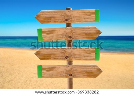 wooden signpost in the meadow with copyspace on the beach - stock photo