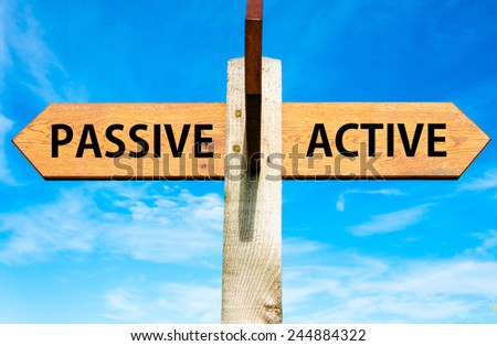 Wooden signpost with two opposite arrows over clear blue sky, Passive versus Active messages, Lifestyle change conceptual image - stock photo