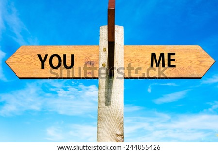 Wooden signpost with two opposite arrows over clear blue sky, You and Me signs, Separation conceptual image - stock photo
