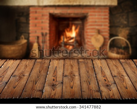 wooden slats table in front of fireplace,winter background - stock photo