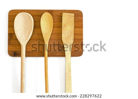 wooden spatula and two spoons on a  cutting board - stock photo