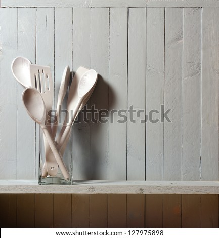 Wooden spatulas and spoons; in glass container against rustic wall; good copy space