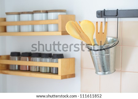 Wooden spatulas in a holder and racks with spices on a kitchen wall