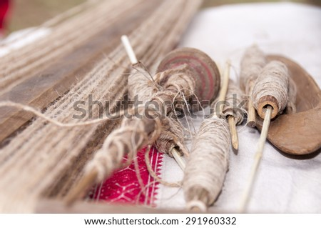 Wooden spindles with flax or hemp threads - stock photo