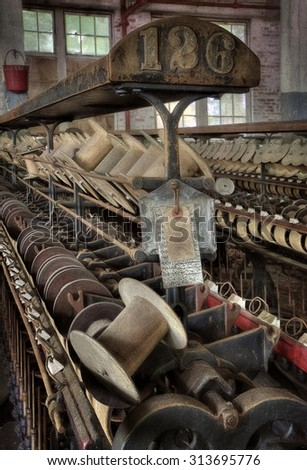 Wooden Spools Sitting on a Loom in the Abandoned Lonaconing Silk Mill in Lonaconing, Maryland - stock photo