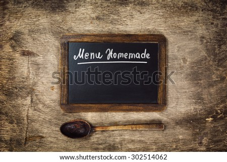 Wooden spoon and Black board on with text - Menu Homemade. Top view - stock photo