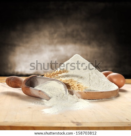 wooden spoon and flour with rye - stock photo