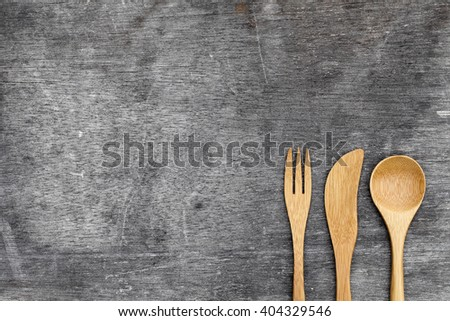 Wooden spoon and fork, knife on grunge wood background
