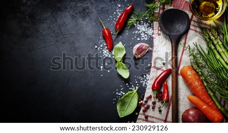 Wooden spoon and ingredients on dark background. Vegetarian food, health or cooking concept. - stock photo