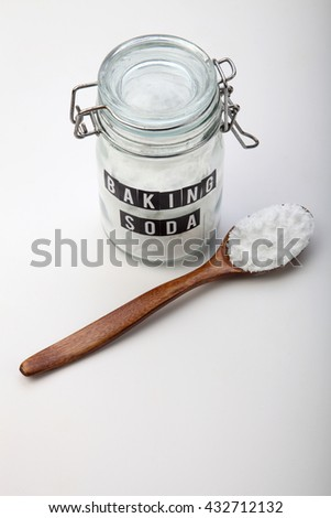 wooden spoon and jar of baking soda - stock photo
