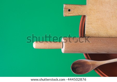 Wooden spoon and other utensils in a crock pot. Green background for a vintage kitchen utensils  set  - stock photo