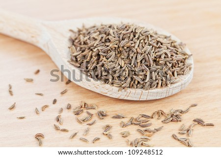 Wooden spoon filled with cumin seeds on the kitchen board - stock photo