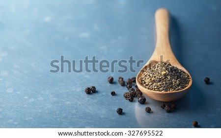 Wooden spoon filled with ground pepper and Black Peppercorns  - stock photo