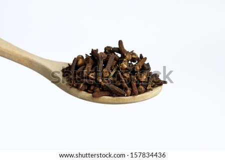Wooden spoon, full of cloves , isolated on white background - stock photo
