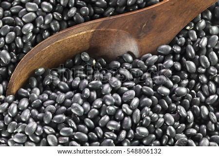 Wooden spoon in dried black beans