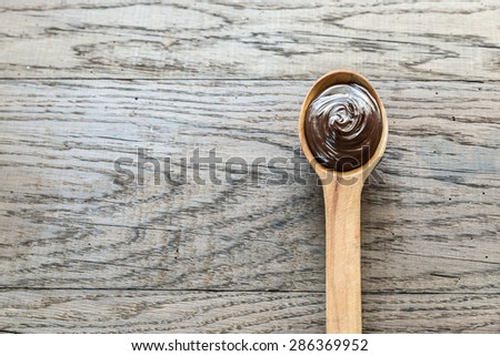 Wooden spoon of chocolate cream with hazelnuts - stock photo