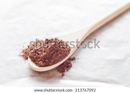 Wooden spoon of cocoa powder - stock photo