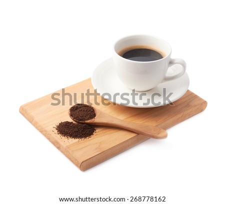 Wooden spoon of ground coffee in front of the cup of a fresh black coffee on a wooden serving board, composition isolated over the white background - stock photo