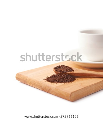 Wooden spoon of ground coffee in front of the cup of a fresh black coffee on a wooden serving board, isolated over the white background and framed as a close-up copyspace background composition - stock photo