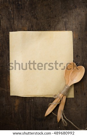 Wooden spoon on table with blank paper