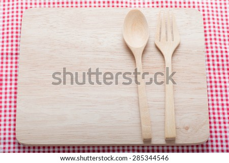 Wooden spoon on wooden cutting board - stock photo