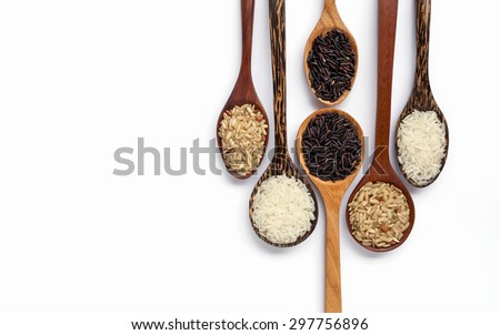 Wooden spoon set and rice on white background