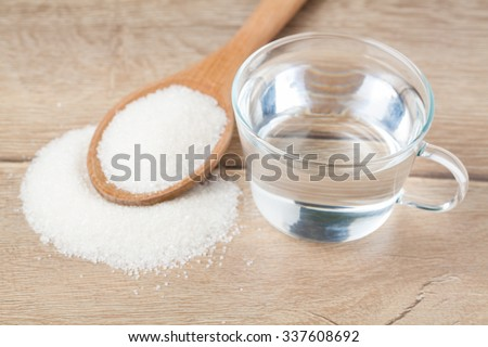 Wooden spoon sugar and glass of water on wood table - stock photo