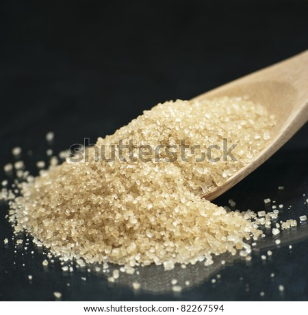 Wooden spoon with brown sugar - stock photo