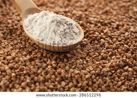 Wooden spoon with buckwheat flour on the background of grains.
