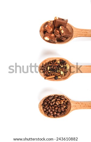 wooden spoon with coffee beans, chocolate and spices for mulled wine, isolated on white - stock photo