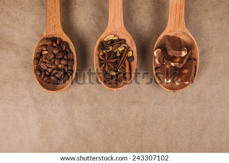 wooden spoon with coffee beans, chocolate and spices for mulled wine lying on brown parchment - stock photo