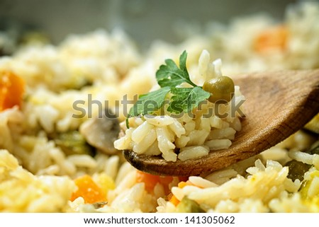 Wooden spoon with cooked rice - stock photo