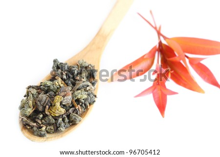 Wooden spoon with dry leaf tea isolated on white, shallow DOF - stock photo