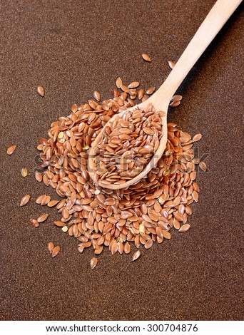 Wooden spoon with flax seeds placed on a metal background - stock photo