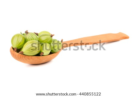 Wooden spoon with fresh green gooseberries on a white background