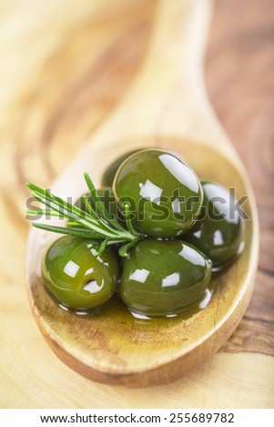 wooden spoon with green olives, olive oil  and some fresh rosemary on a cutting board - stock photo