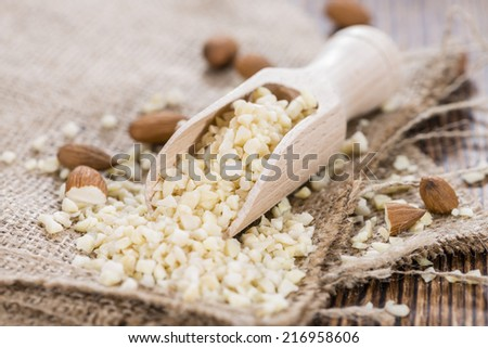 Wooden Spoon with Minced Almonds (on rustic background) - stock photo