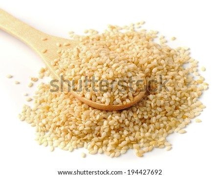 Wooden spoon with sesame seeds on a white background - stock photo