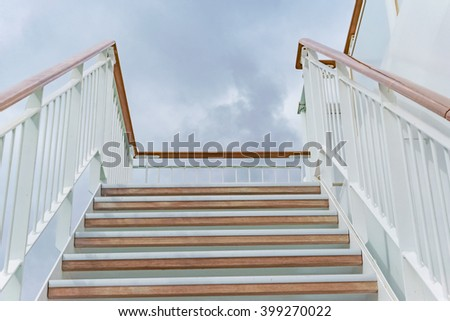 Wooden stairs against cloudy background  White metal stair-rail with wooden handrail - stock photo