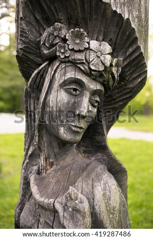 wooden statue of a woman in a wreath - stock photo