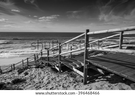 wooden steps leading down to a beautiful wild and deserted beach on portugal's atlantic coast at sunset - stock photo