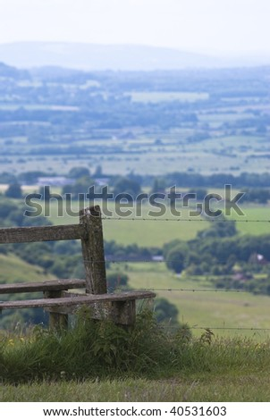 Wooden stile in the foreground with barbed wire fence, beneath which are grasses, nettles and flowers. Bordered land and trees are visible in background. Vertical orientation (portrait)