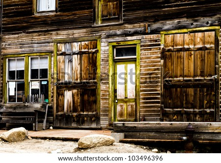 Wooden storefront of an old mining ghost town that is weathered. - stock photo