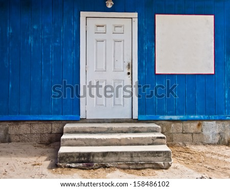 Wooden structure painted dark blue with a white door and a blank white sign that can be used for copy.  there are three stone stairs leading to the door - stock photo