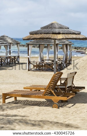 Wooden sunbeds and straw umbrella in front of beautiful bungalows for relaxation on the Mediterranean sea sand beach in Paphos, Cyprus. - stock photo