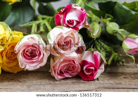 Wooden surface decorated with colorful roses - stock photo